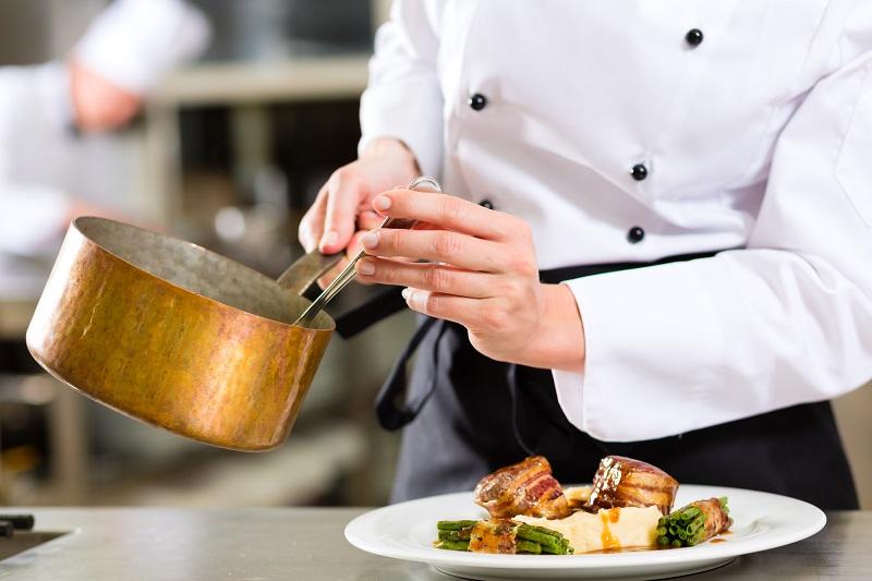 Chef in hotel or restaurant kitchen cooking