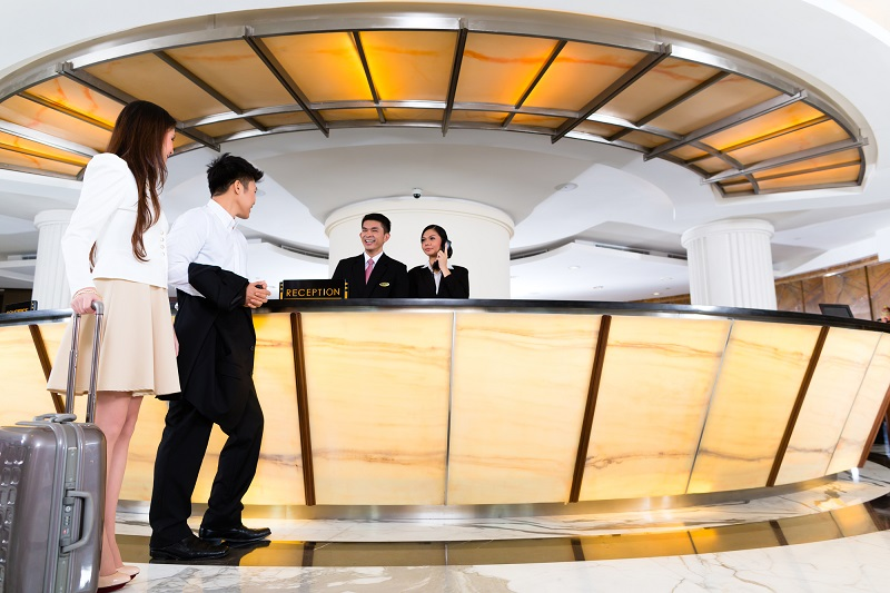 Asian Chinese couple arriving at hotel front desk